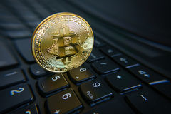 Golden bitcoin coin on the black laptop keyboard. Stock Images