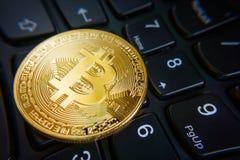 Golden bitcoin coin on the black laptop keyboard. Royalty Free Stock Photos