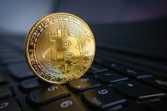 Golden bitcoin coin on the black laptop keyboard. Stock Photos