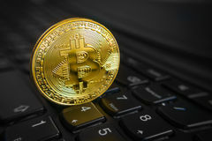 Golden bitcoin coin on the black laptop keyboard. Royalty Free Stock Photography