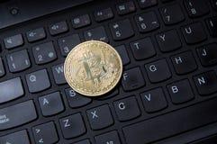 Golden bitcoin coin on black qwerty desktop keyboard. Close-up of a golden bitcoin coin on a qwerty desktop keyboard royalty free stock photos