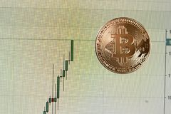 Golden bitcoin coin on a chart of currency growth. Golden bitcoin coin on a chart of currency growth Royalty Free Stock Photos