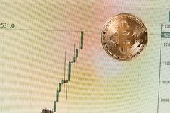 Golden bitcoin coin on a chart of currency growth. Golden bitcoin coin on a chart of currency growth Royalty Free Stock Photo