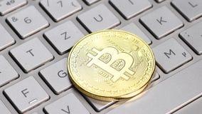 Golden bitcoin coin. Bitcoin cryptocurrency. Golden coin on laptop keyboard, macro shot stock footage