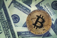 Golden bitcoin coin on dollar bills background. Cryptocurrency and cash money banking concept. Toned royalty free stock images