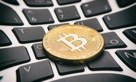Golden bitcoin coin on keyboard Stock Photos