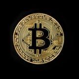 Golden bitcoin coin on a black background. Golden bitcoin coin lying on a black background Royalty Free Stock Photos