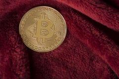 Golden bitcoin coin on a burgundy red velvet background. Golden bitcoin coin lying on a burgundy red velvet background Royalty Free Stock Image