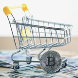 Golden bitcoin coin near shopping cart - symbol of crypto currency. Concept of purchases for bitcoin stock images