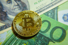 Golden bitcoin coin on the one hundred dollars banknote. Royalty Free Stock Photo