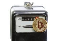 Golden BitCoin coin over an electric power meter. Big golden BitCoin coin over an old analog electric power meter Stock Photos