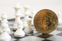 Golden bitcoin coin symbolizes elements with chess board. Golden bitcoin coin symbolizes elements of virtual economy or crypto currency with chess board royalty free stock image