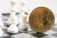 Golden bitcoin coin symbolizes elements with chess board. Golden bitcoin coin symbolizes elements of virtual economy or crypto currency with chess board stock photo