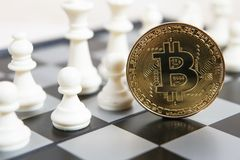 Golden bitcoin coin symbolizes elements with chess board. Golden bitcoin coin symbolizes elements of virtual economy or crypto currency with chess board royalty free stock photo