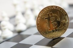 Golden bitcoin coin symbolizes elements with chess board. Golden bitcoin coin symbolizes elements of virtual economy or crypto currency with chess board royalty free stock photography