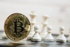 Golden bitcoin coin symbolizes elements with chess board. Golden bitcoin coin symbolizes elements of virtual economy or crypto currency with chess board stock image