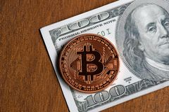 Golden bitcoin coin on us dollars close up. Cryptography, cash royalty free stock images