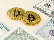Golden bitcoin coin on us dollars close up. Royalty Free Stock Image