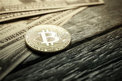 Golden bitcoin coin on and us dollars on wood table. Stock Photo