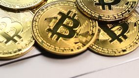 Golden bitcoin coins. Bitcoin cryptocurrency. Golden coins on laptop keyboard, macro shot with tilt stock footage