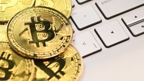 Golden bitcoin coins. Bitcoin cryptocurrency. Golden coins on laptop keyboard, macro shot with panning stock footage