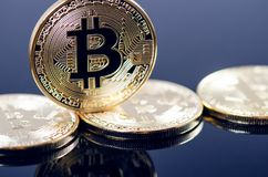 Golden bitcoin coins on a dark background with reflection. Virtual currency. Crypto currency. New virtual money. Stock Images