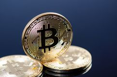Golden bitcoin coins on a dark background with reflection. Virtual currency. Crypto currency. New virtual money. Stock Photo