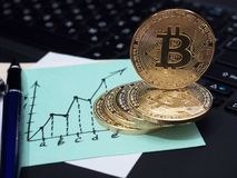 Golden Bitcoin coins on the laptop keyboard. Business note in the form of a graph. stock images