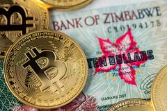 Golden Bitcoin coins new virtual money on Zimbabwe hyperinflation banknote close up image. stock photography