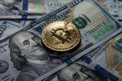 Golden bitcoin coins on a paper dollars money and dark background with sun. Virtual currency. Crypto currency mining. New virtual. Golden bitcoin coins on a stock image