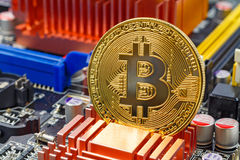 Golden bitcoin on the computer motherboard background closeup. Cryptocurrency virtual money Stock Image