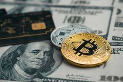 Golden bitcoin with credit card on top of dollar banknote backgr. Ound, new currency, accepting bitcoin for payment, finance concept Stock Image