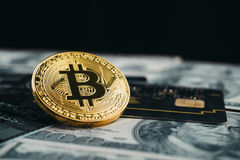 Golden bitcoin with credit card on top of dollar banknote background, new currency, accepting bitcoin for payment, finance concept royalty free stock photography