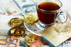Golden Bitcoin Crypto currency coin on dollar, euro banknotes background and credit card near cup of coffee. Investments. Cryptocurrency digital payment stock images