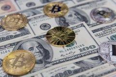 Golden bitcoins on one hundred dollar bills stock photo
