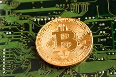 Golden Bitcoin Cryptocurrency on circuit board. Golden Bitcoin Cryptocurrency on computer circuit board. Macro shot Royalty Free Stock Photo