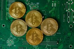 Golden Bitcoin Cryptocurrency On Computer Circuit Board CPU. Golden Bitcoin Virtual Money On Digital Circuit Board Computer. Concept Of Blockchain Technology stock photography