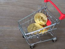 Golden bitcoin cryptocurrency in red shopping cart on desk wood background. Digital money cryptocurrency concept Stock Photo