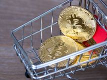 Golden bitcoin cryptocurrency in red shopping cart on desk wood background. Digital money cryptocurrency concept Stock Photography