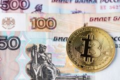 Golden Bitcoin cryptocurrency on Russian Rubles banknotes. stock photos