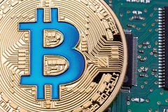 Golden Bitcoin currency on a circuit board background. High resolution photo Stock Photos
