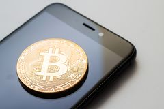 Close-up of a golden bitcoin currency and a smart phone Stock Photography