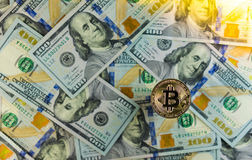 Golden Bitcoin on Dollar bills background. Stock Image