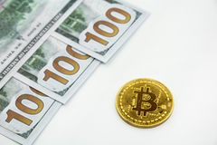 Golden bitcoin and 100 dollars. Bills on a white background Royalty Free Stock Images