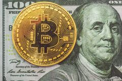 Golden bitcoin and 100 dollars. Golden bitcoin coin and 100 dollars bills on a white background Royalty Free Stock Photo