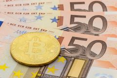 Golden Bitcoin on 50 Euro. Electronic money exchange concept Royalty Free Stock Images