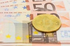 Golden Bitcoin on 50 Euro. Electronic money exchange concept Royalty Free Stock Photos