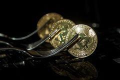 Golden bitcoin with fork and two blurred bitcoins above.Hard for Stock Image