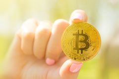 Golden bitcoin in generation alpha kids hand, uncertainty future life with bitcoin in hand Royalty Free Stock Images