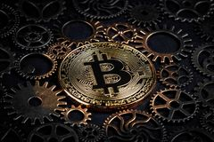 Golden bitcoin glowing in the middle of intricate cog wheels closeup. Crypto currency concept. Royalty Free Stock Photos